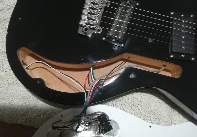 Guitare électrique avec le pickgard enlevé et la cavité non blindée